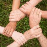 Sechs Hände bilden eine Sechseck, halten gegenseitig am Handgelenk
