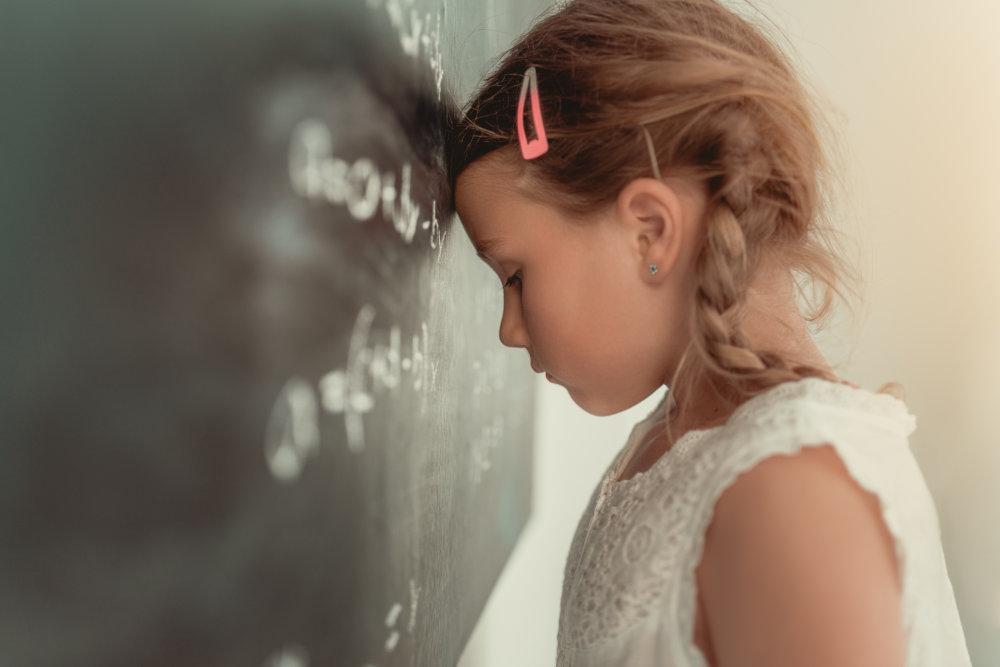 Mädchen lehnt mit Kopf an einer Tafel ist gestresst von Aufgaben