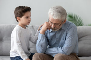 Junge tröstet einen traurigen älteren Mann auf einem Sofa sitzend