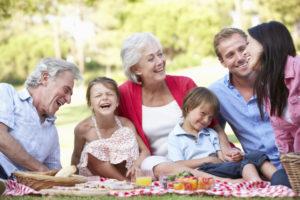 Mehrgenerationenfamilie lacht bei einem Picnic im Park