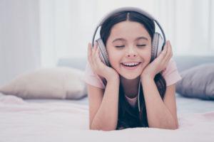 Mädchen hört Fantasiereisen mit Kopfhören auf dem Bett liegend