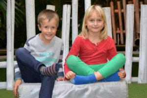 Zwei Kinder (Junge und Mädchen) sitzen auf einer Bank im Garten und versuchen zu meditieren