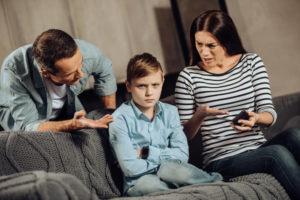 Eltern diskutieren mit ihrem Sohn über Handynutzung